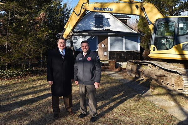 Two men standing beside home to be demolished