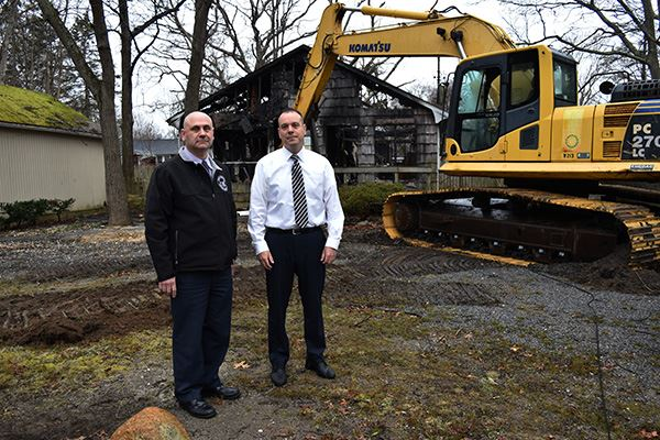 Two men and crane at home to be demolished