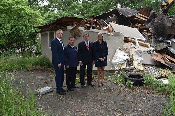 Four people in front of demolished home