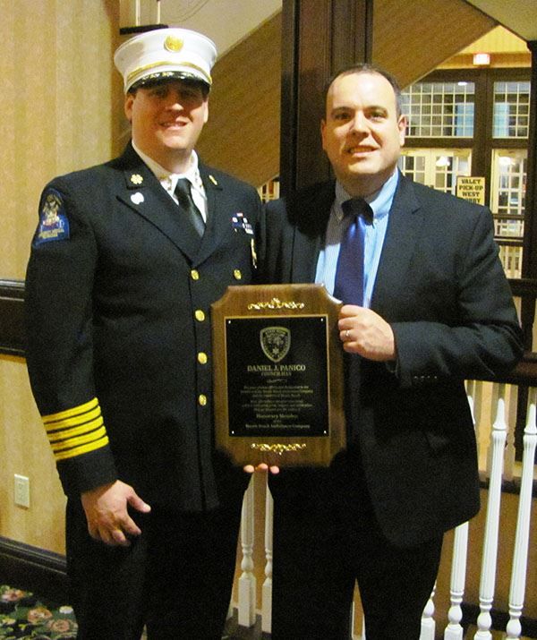 Man in uniform presenting award to business man