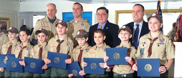 Young boy scouts holding awards in line