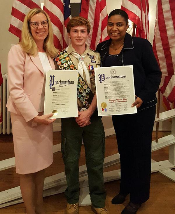 Boy Scout standing between two councilwomen