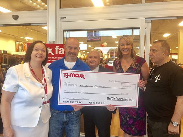 Five people at TJMaxx with giant check