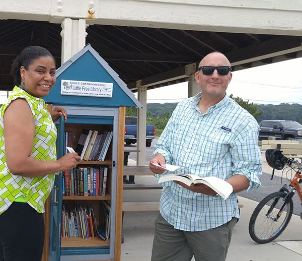Man and woman beside Little Free Library